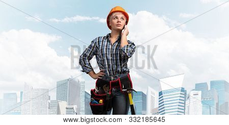 Attractive blonde woman in workwear and hardhat talking on smartphone. Portrait of young worker in checkered blue shirt standing on cityscape background. Business communication and conversation. poster