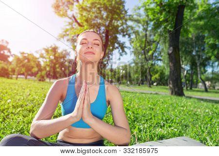 Girl Meditates In Lotus Pose On Green Grass At Sunrise. Practicing Of Yoga. Portrait Of Young Woman