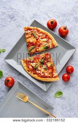 Two Pieces Of Vegetarian Pizza On Light Blue Background