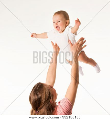 Young Happy Mom Throws Up Her Charming Baby On A White Background In The Studio. Concept Of Little H