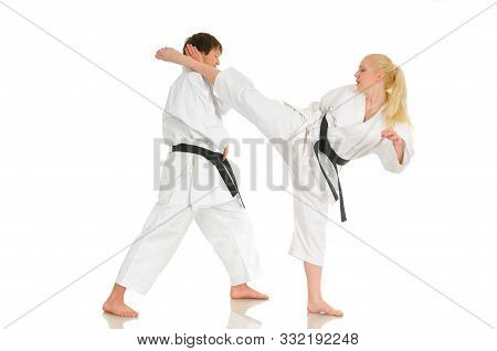 Blonde Young Girl And A Young Cheeky Guy Karateka Are Engaged In Training In A Kimono On A White Bac