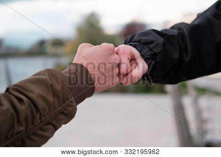 Fist Bump Close-up. Young People Say Hello Fist Outdoors Fist. Friendship. Youth. A Game