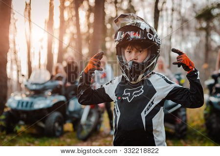 A Child On A Motorcycle. The Little Biker Is Wearing A Protective Suit And Helmet. Russia Moscow 18