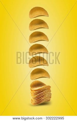 Potato Crisps Falling Down Against A Yellow Background With Copy Space For Text Or Images. Crispy, P