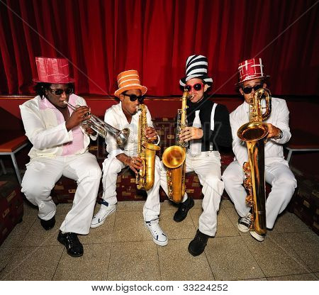 Portrait of four funky musicians playind wind instruments, saxo, trumpet.