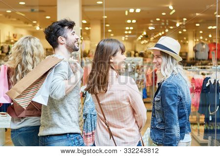 Young people shopping together in front of a fashion shop