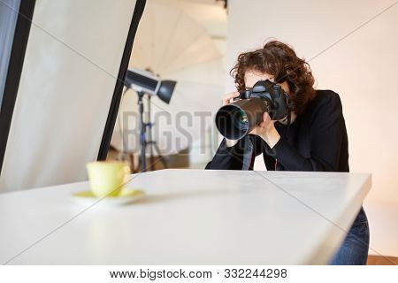 Photographer with SLR camera taking a picture of a product