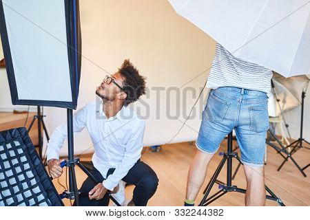 Photo assistants team in the photo studio preparing a photo shoot