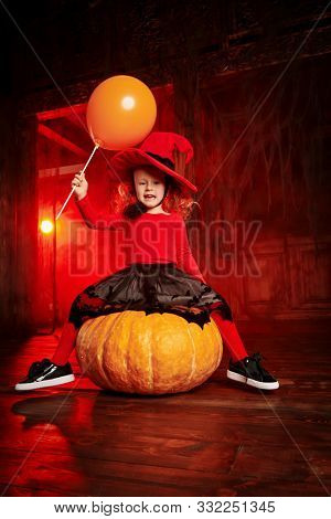 Funny little girl in a witch costume sits on a big pumpkin in an old house and screams in fright. Halloween.