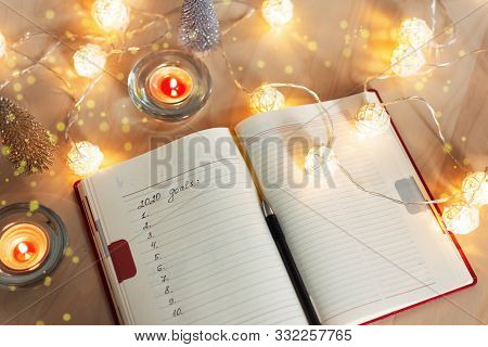 New Year's Goals With Christmas Decorations And Candles.