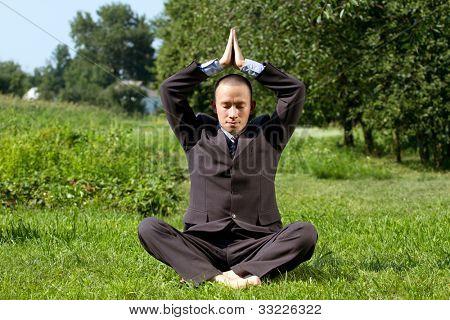 Man businessman meditating outdoors in lotus pose