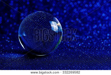 Crystal Ball With Magic Mirror Reflection In Bokeh Blue.