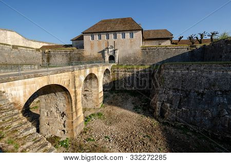 View Of The Old Citadel In The City Of Besancon, France. There Is A Bridge Across A Deep Moat And En