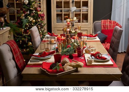 Beautiful table setting with Christmas decorations in living room. Xmas Decoration.