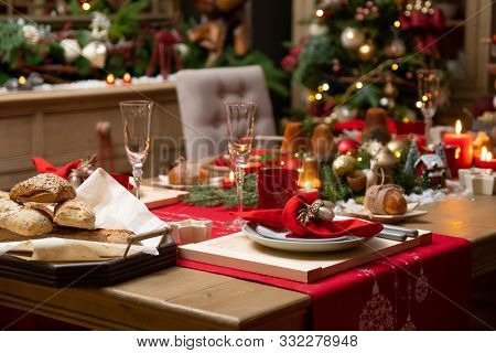 Beautiful table setting for Christmas party or New Year celebration. Beautiful served table with candles, red napkins, white china, silver cutlery, crystal champagne glasses.