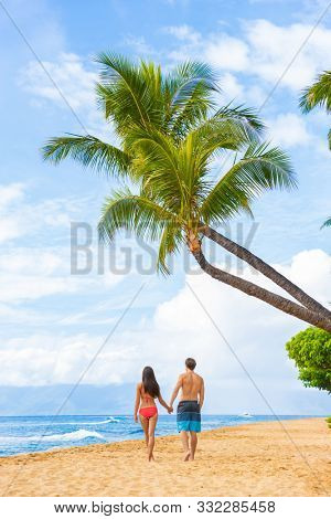 Hawaii beach couple walking on Kaanapali Maui Hawai travel. Two adults tourist on sunset stroll romantic vacation travel holiday. Vertical shot with palm trees tropical background. poster