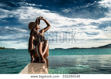 Elegant luxury black swimsuit swimwear model woman with sun hat on infinity pool resort vacation. Europe holiday hotel for wellness spa, hair removal laser legs and body care.