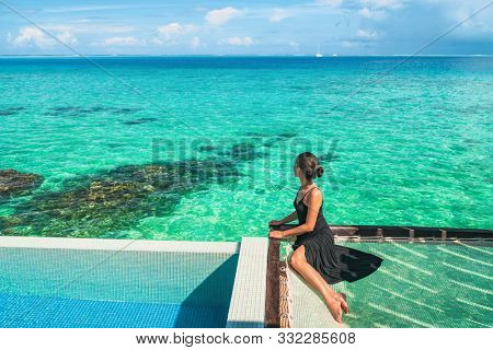 Luxury resort vacation in Bora Bora ,Tahiti, French Polynesia elegant lady tourist woman relaxing looking at turquoise ocean view from hotel room overwater bungalow honeymoon suite travel lifestyle.