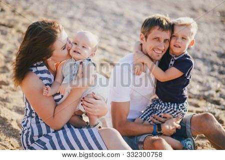 Happy Family With Two Kids Having Fun Near Sea At The Beach.