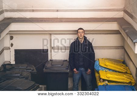 Portrait Of A Casual Young Man With Closed Eyes Standing Between Garbage Cans
