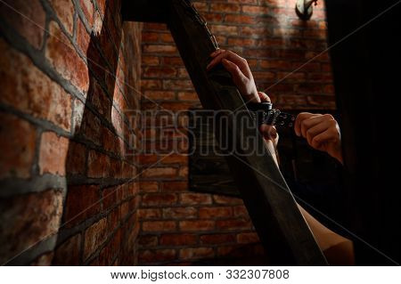Bdsm Close-up Of Hands In Handcuffs. The Man Dominates And Rivets His Mistress To The Andreev Cross.