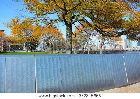 NEW YORK, NY - 04 NOV 2019: The American Immigrant Wall of Honor at Ellis Island, with colorful fall trees. colorful,