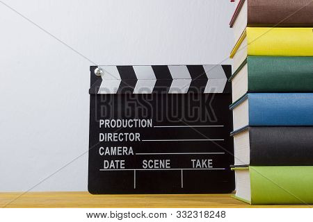 A Stack Of Books With Multi-colored Binders And A Movie Clapper On A Wooden Table