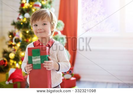 Little Boy Hold A Gift Box Near A Decorated Christmas Tree At Home Decorating And Christmas Tree