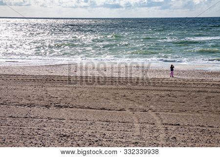 Cute Little Girl Playing On The Sandy Beach. Happy Child Wearing Warm Floral Print Jacket, Pom Pom H
