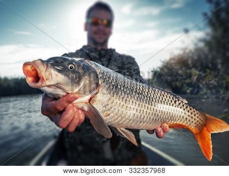 Young angler holds the big Carp fish (Cyprinus carpio) being in the boat on the river. Tilt shif effect applied, focus on the fish