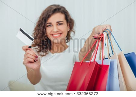 Blurred Cheerful Kinky Girl With Shining Smile Is Extending Four Colorful Shop Bags In One Hand And