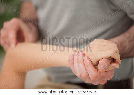 Arm of a woman being manipulated in a room