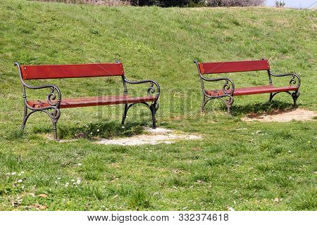 Two Red Wooden Bench In Beautiful Natural Environment, Grass And Spring Flowers. Benches In Public P