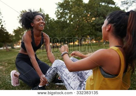 Cheerful Young Diverse Female Friends Laughing Doing Ab Crunches On Green Grass In The Park - Friend