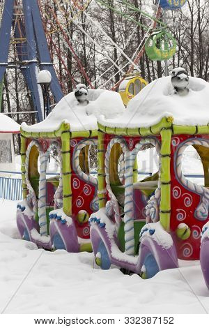 An Empty Amusement Park In Winter, A Multi-colored Carousel Steam Engine Under A Thick Layer Of Snow