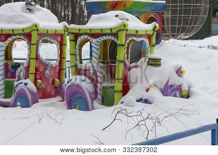 Closed Amusement Park In Winter, A Multi-colored Steam Carousel With Wagons Covered With A Thick Lay