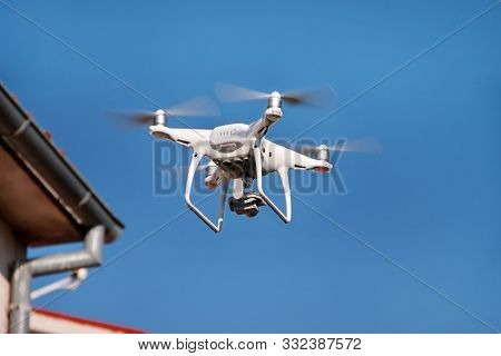 Drone Quad Copter Fly On Blue Sky In Background. Modern Drone Is Flying In Air, To Take Photos And R