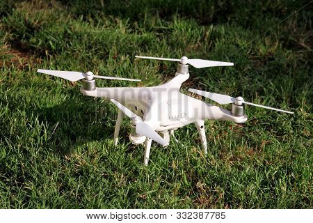 White Quadcopter Drone With 4k Digital Camera On Grass Is Ready For Take Off To Fly In Air To Take P