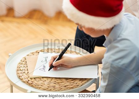 Xmas Gifts Wishlist. Boy Writing Letter To Santa Claus Sitting On Sofa At Home. Selective Focus