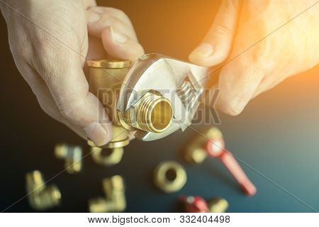 Plumber Hands Screwing Nut Of Pipe Over Plumbing Tools Background. Concept Of Repair And Technical A
