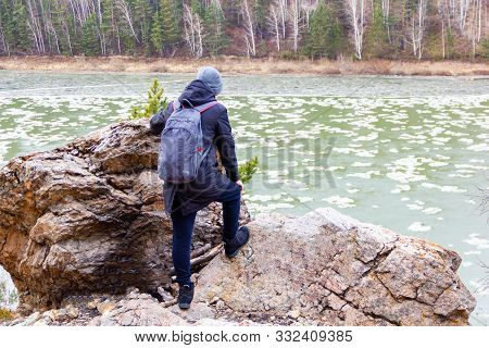 A Tourist With A Backpack Looks From The Cliff At The River, On Which Ice Floats