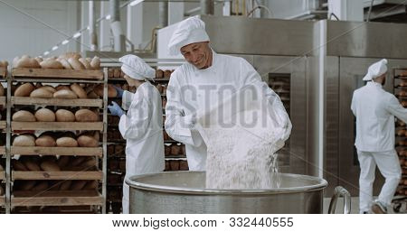 Big Bakery Industry Baker Prepare The Dough Add The Flour In A Big Container Background Workers Arra