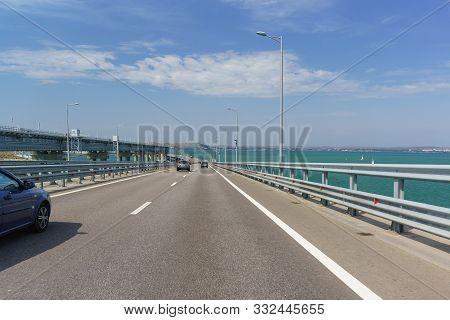 Crimean Bridge Across The Kerch Strait. Cars Descend From The Height Of The Navigable Arch Span. Ahe
