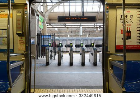 NEWARK, NJ - 05 NOV 2019: View from inside a Path Train with the doors open looking onto the paltform with turnstiles and passing train.