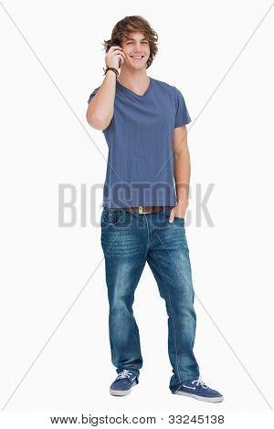Gelukkig mannelijke student op de telefoon tegen witte achtergrond