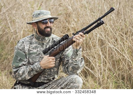 The Smiling Hunter In Military Uniform Is Holding Rifle Weapon Or Airgun And Squatting In Nature.