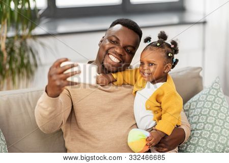 family, fatherhood and people concept - happy african american father with little baby daughter taking selfie by smartphone at home