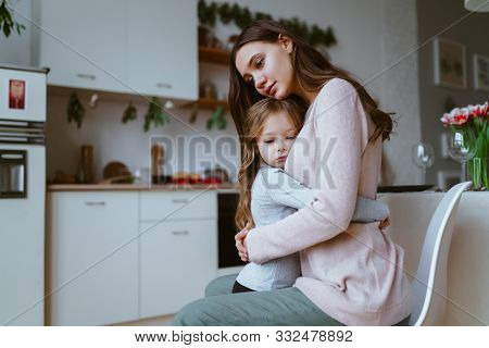 Mom Hugged Her Daughter In The Kitchen, Both Faces Have An Expression Of Quiet Sadness Or Sadness