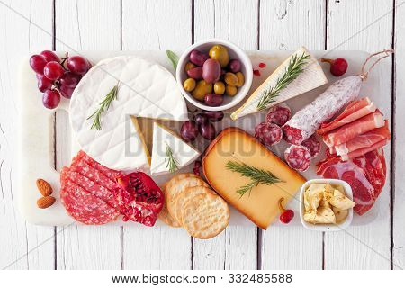 Serving Platter Of Assorted Meats, Cheeses And Appetizers. Top View On A White Wood Background.