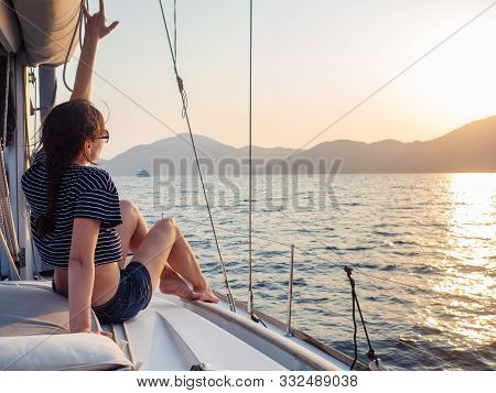 Attractive Young Woman In A Striped T-shirt Enjoys The Sunset On The Deck Of A Sailing Yacht. Sailin